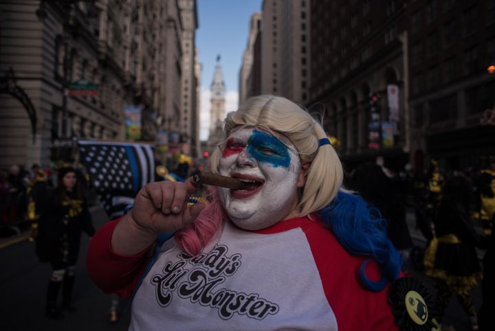 A reveler smokes a cigar as he poses for a photo in fancy dress during the annual Mummers Parade in Philadelphia. The annual