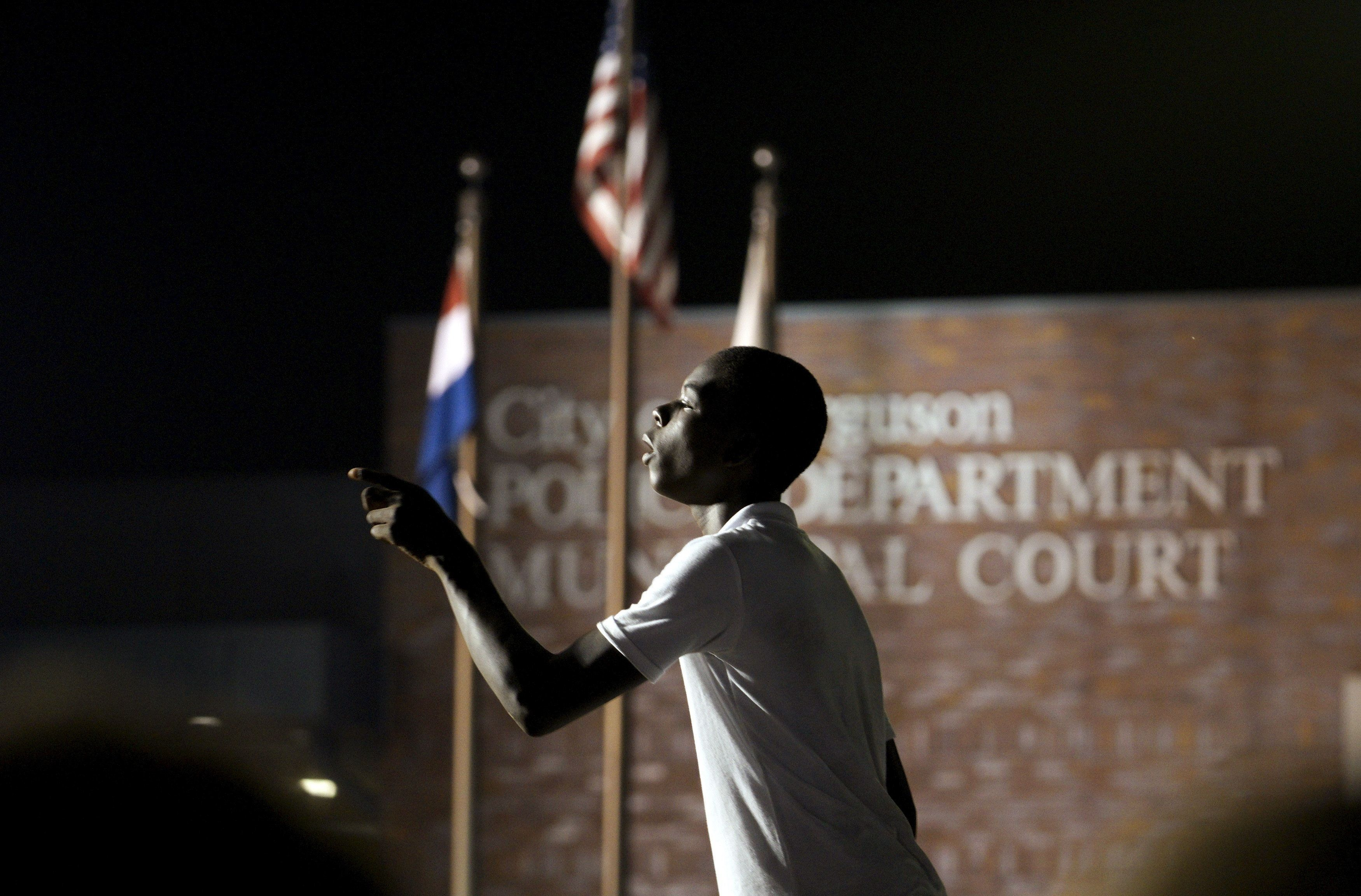 A protester yells at police stationed outside the police department in Ferguson, Missouri August 8, 2015.  One year after the police shooting of an unarmed black teen thrust Ferguson, into the national spotlight, the St. Louis suburb is bracing for a weekend of protests over continued complaints of police violence.  REUTERS/Rick Wilking