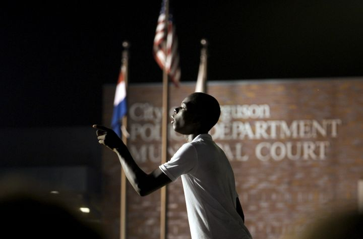 A protester yells at police stationed outside the police department in Ferguson, Missouri, on Aug. 8, 2015. The shooting deat