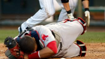 Boston Red Sox catcher Victor Martinez (foreground) lies stunned after a home plate collision with Colorado Rockies runner Clint Barmes (background) who tags the plate to score a run in the fourth inning in their interleague MLB baseball game in Denver June 23, 2010. REUTERS/Rick Wilking (UNITED STATES - Tags: SPORT BASEBALL)