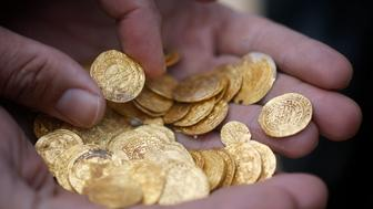Ancient gold coins are displayed in Caesarea, north of Tel Aviv along the Mediterranean coast February 18, 2015. Almost 2,000 gold coins, believed to be from the 11th century, were found in recent weeks on the seabed by amateur divers who then alerted the Israel Antiquities Authority's Marine Archaeology Unit.  REUTERS/Nir Elias (ISRAEL - Tags: MARITIME SOCIETY)