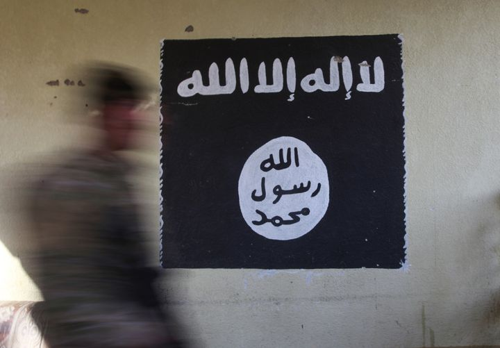 A member of the Iraqi rapid response forces walks past a wall painted with the black flag commonly used by Islamic State mili