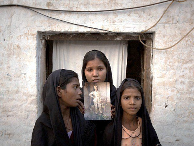 <p>The daughters (now in hiding) of Aasia Bibi with an image of their mother, standing outside their residence.</p>