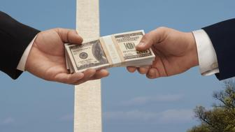 Two hands exchanging a stack of money in Washington DC with the Washington monument and capitol Hill in the background