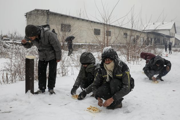 Migrants eat free food during a snowfall outside a derelict customs warehouse in Belgrade, Serbia January...