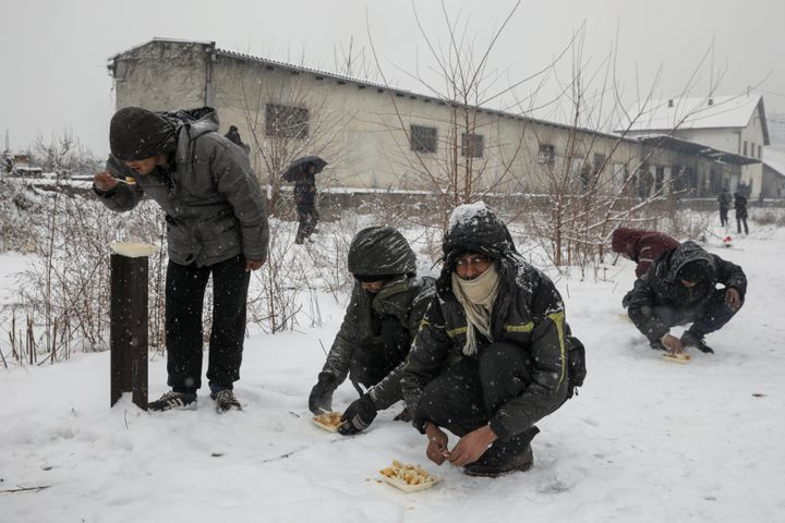 Migrants eat free food during a snowfall outside a derelict customs warehouse in Belgrade, Serbia January 9, 2017.