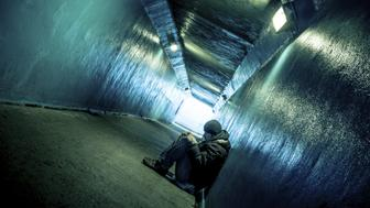 Homeless young man sitting in subway tunnel.