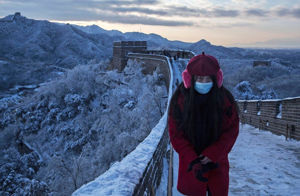 A Chinese tourist walks on a slippery section of ice as snow is seen on the Great Wall after a snowfall on Nov. 23, 2015