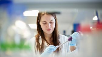 Female science student pipetting in laboratory