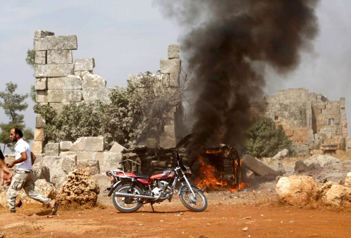 A man runs past a burning military vehicle at a base controlled by rebel fighters from the Ahrar al-Sham Movement, that was t