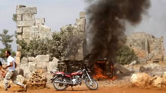 A man runs past a burning military vehicle at a base controlled by rebel fighters from the Ahrar al-Sham Movement, that was targeted by what activists said were Russian airstrikes, at Hass ancient cemeteries in the southern province of Idlib, Syria October 1, 2015. REUTERS/Khalil Ashawi
