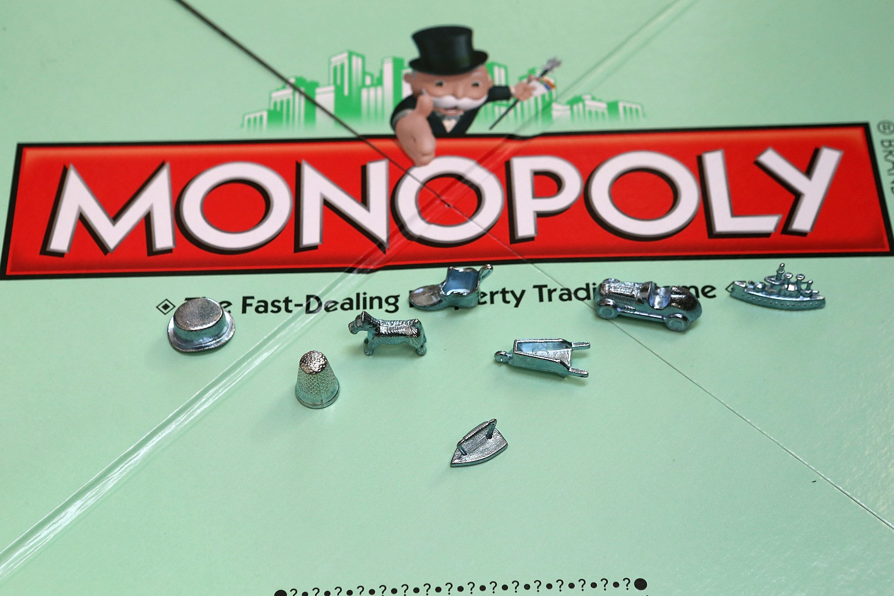 FAIRFAX, CA - FEBRUARY 06:  In this photo illustration, Monopoly game pieces are displayed on February 6, 2013 in Fairfax, California. Toy maker Hasbro, Inc. announced today that fans of the board game Monopoly voted in an online contest to eliminate the iron playing figure and replace it with a cat figure. The cat game piece received 31 percent of the online votes to beat out four other contenders, a robot, diamond ring, helicopter and guitar.  (Photo illustration by Justin Sullivan/Getty Images)