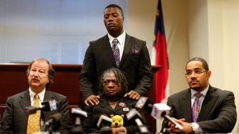 Attorney Charles Monnett (L) speaks regarding Jonathan Ferrell, the 24-year-old former FAMU football player who was shot and killed in September 2013, as mother Georgia Ferrell (C), brother Willie Ferrell (standing) and attorney Chris Chestnut (R) look on during a news conference in Charlotte, North Carolina January 14, 2014. Prosecutors will seek an indictment against a North Carolina police officer, Randall Kerrick, accused of fatally shooting an unarmed Ferrell 10 times after he survived a car accident and banged on the door of a nearby house in the middle of the night looking for help. REUTERS/Chris Keane (UNITED STATES - Tags: CRIME LAW)