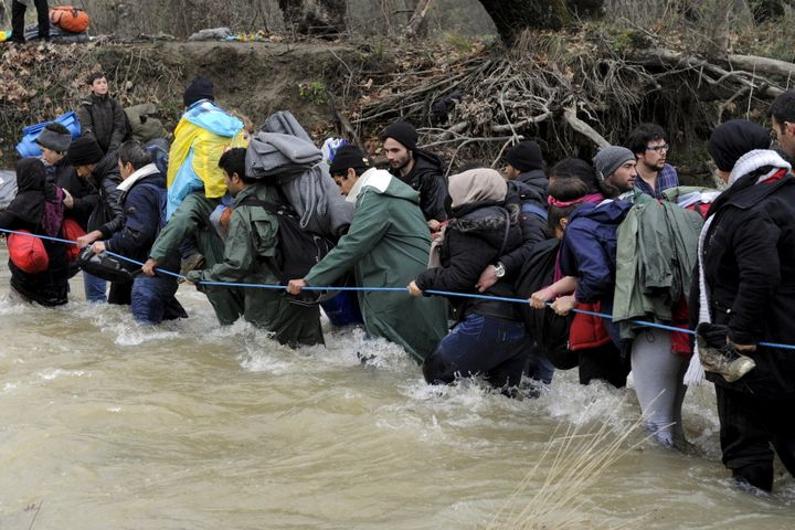 Migrants and refugeeswade across a river near the Greek-Macedonian border, west of the the village of Idomeni, Greece,