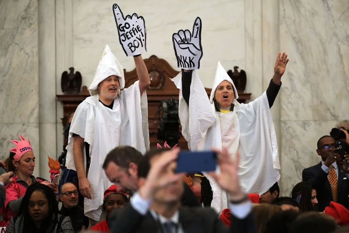 Protesters wearing white sheets shout at Sessions as he arrives for his confirmation hearing.