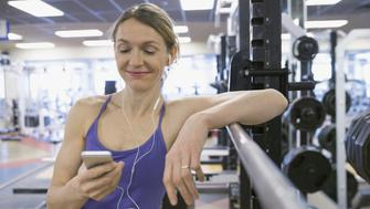 Smiling woman listening to mp3 player at gym