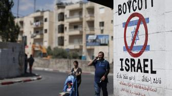 Palestinians walk past a sign painted on a wall in the West Bank biblical town of Bethlehem on June 5, 2015, calling to boycott Israeli products coming from Jewish settlements. The international BDS (boycott, divestment and sanctions) campaign, that pushes for a ban on Israeli products, aims to exert political and economic pressure over Israel's occupation of the Palestinian territories in a bid to repeat the success of the campaign which ended apartheid in South Africa. AFP PHOTO / THOMAS COEX        (Photo credit should read THOMAS COEX/AFP/Getty Images)