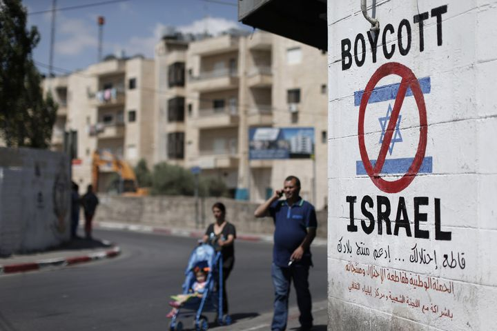 Palestinians walk past a sign painted on a wall in the West Bank town of Bethlehem calling to boycott Israeli products coming