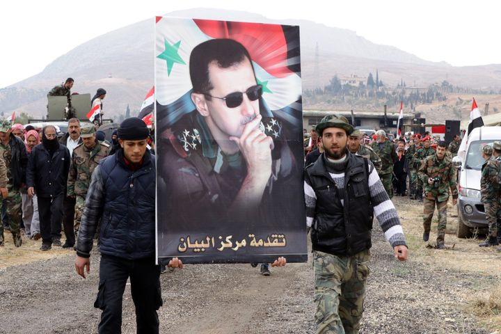 Syrian volunteers and their relatives wave the national flag and portraits of President Bashar al-Assad.
