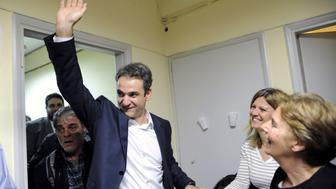 Kyriakos Mitsotakis, the newly elected leader of Greece's conservative New Democracy party, greets his supporters during his exit from his office in Athens, Greece, after winning the party elections January 11, 2016. REUTERS/Michalis Karagiannis