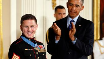 """U.S. President Barack Obama applauds after presenting the Medal of Honor to retired U.S. Marine Corps Corporal William """"Kyle"""" Carpenter during a ceremony at the White House in Washington June 19, 2014. Obama presented Carpenter the Medal of Honor, the highest U.S. award for gallantry, on Thursday for covering a grenade with his body and saving a comrade's life.   REUTERS/Kevin Lamarque  (UNITED STATES - Tags: POLITICS MILITARY)"""