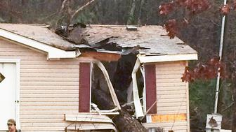 A storm damaged house is pictured outside of Atkins, Arkansas in this December 23, 2015 handout photo. High winds and heavy rain caused a large tree to become uprooted and fall on the house, trapping an 18-year-old woman and an 18-month-old toddler. Emergency personnel were able to rescue the toddler, but the woman was pronounced dead.  Southern U.S. states began digging out December 24 after severe storms including some 20 tornadoes killed at least 10 people.  The storm system on Wednesday packed high winds and triggered more than 20 tornadoes in Arkansas, Illinois, Indiana, Mississippi, Tennessee and Michigan, authorities said.  REUTERS/Pope County Sheriff's Office/Handout via Reuters   FOR EDITORIAL USE ONLY. NOT FOR SALE FOR MARKETING OR ADVERTISING CAMPAIGNS.  THIS PICTURE WAS PROCESSED BY REUTERS TO ENHANCE QUALITY. AN UNPROCESSED VERSION WILL BE PROVIDED SEPARATELY