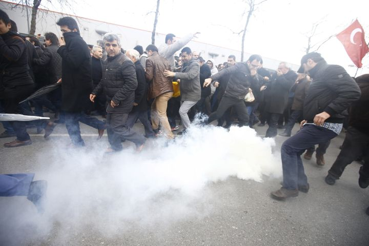 Riot police use tear gas to disperse protesting employees and supporters of Zaman newspaper at the courtyard of the newspaper