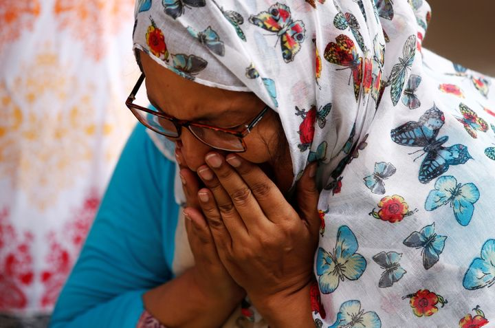 A woman mourns for the victims who were killed in the attack on the Holey Artisan Bakery and the O'Kitchen Restaurant, at a m