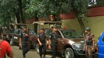 Rapid Action Battalion members walk as police stormed the Holey Artisan restaurant after gunmen attacked it and took hostages early on Saturday in Dhaka, Bangladesh in this still frame taken from live video July 2, 2016. REUTERS/ REUTERS TV