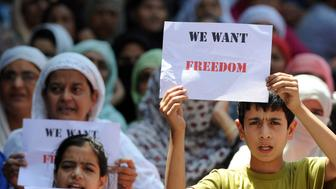 Young Kashmiri protestors hold placards at a protest against civilian killings in Kashmir's ongoing summer unrest, during a curfew in the Batmaloo area of Srinagar on August 17, 2016.  Suspected militants killed two soldiers and one police officer in an ambush on a convoy overnight in Indian-administrated Kashmir, an official in the troubled region said. An unknown number of gunmen opened fire on the two army trucks and a police car travelling through Baramulla district, 60 kilometres (37 miles) west of the region's main city of Srinagar.Kashmir has been under curfew since protests erupted over the death last month of a popular young rebel leader, Burhan Wani, in a gunfight with security forces.   / AFP / TAUSEEF MUSTAFA        (Photo credit should read TAUSEEF MUSTAFA/AFP/Getty Images)