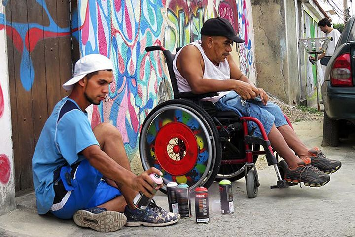 An unidentified artist paints the wheels of a wheel chair. Meeting  Of Favela 2016. Favela Operaria. Duque de Caxias. Rio De