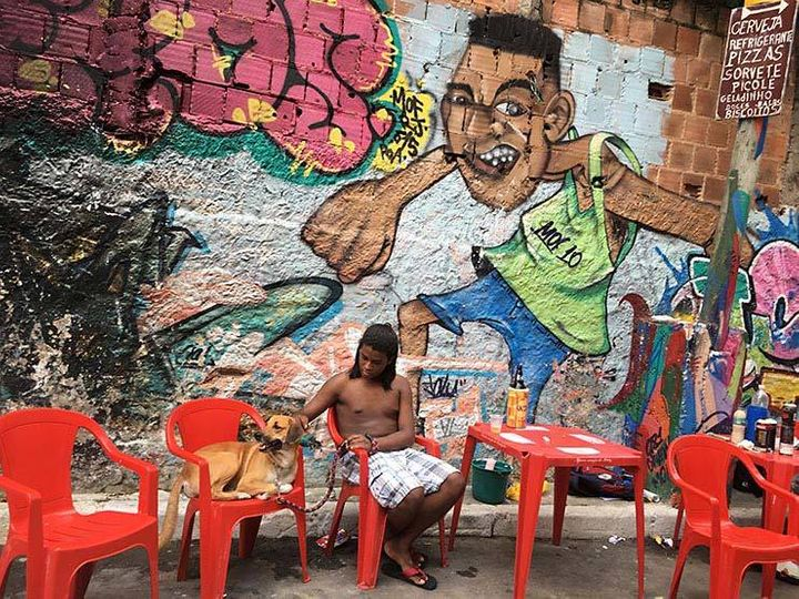 Sergio with his dog Thor. In the background a mural painted by Talu for last year's MOF. Meeting Of Favela 2016. Favela Opera
