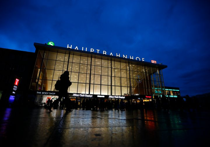 People are silhouetted as they walk past the main railway station in Cologne, Germany, January 5, 2016.
