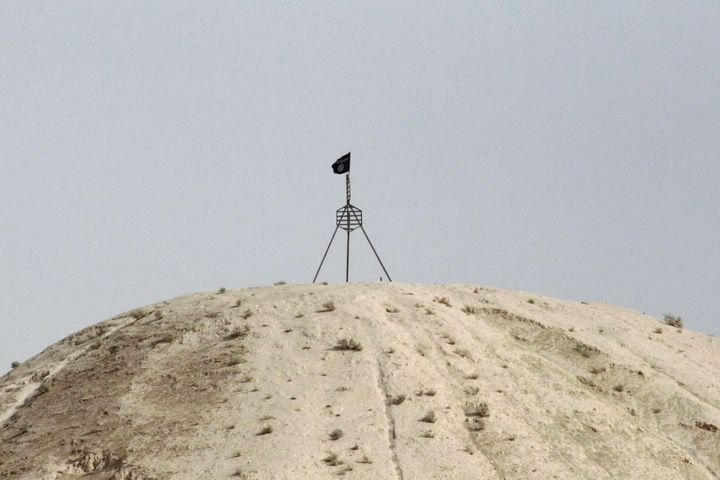 A fluttering Islamic State flag, is flown over a hill in Tel Abyad town on the Syrian-Turkish border.