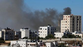 Smoke rises during an Israeli military operation in the West Bank city of Hebron September 23, 2014. Israeli troops shot dead two Palestinians in the West Bank city of Hebron on Tuesday and the military said they were members of Hamas responsible for the killing of three Israeli youths in June, an attack that led to the Gaza war. Marwan Kawasme and Amar Abu Aysha, both in their 30s, were shot dead during a gun battle after Israeli troops surrounded a house in the city before dawn, the army and residents said. Israel had been hunting the men for three months. REUTERS/Ammar Awad (WEST BANK - Tags: POLITICS CIVIL UNREST)