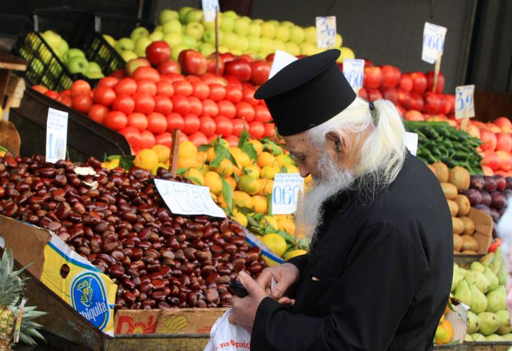 A Greek orthodox priest searches for change to buy vegetables in Athens November 8, 2011.