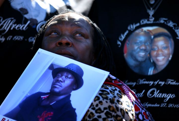 A woman holds a picture of Alfred Olango during a rally and march to protest the fatal police shooting of the Ugandan immigra