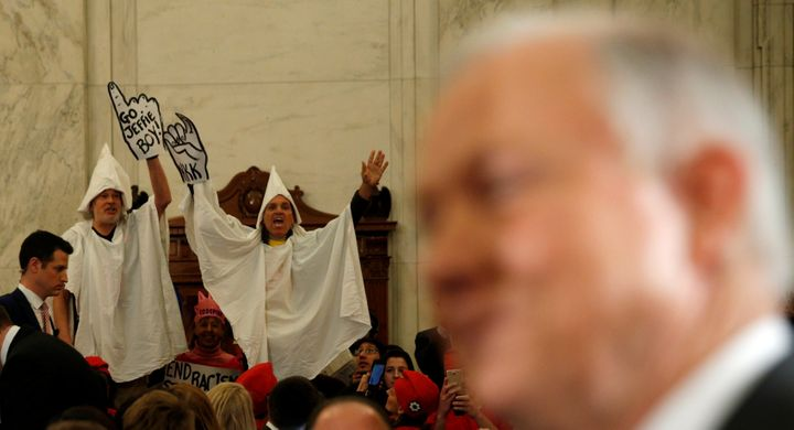 Protesters dressed as Klansmen disrupt the start of a Senate Judiciary Committee confirmation hearing for U.S. Attorney Gener