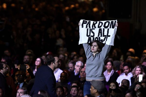 "A protester holds up a sign reading ""Pardon Us All Now!"""