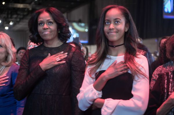 First lady Michelle Obama (left) and daughter Malia listen to the national anthem before President Barack Obama delivers his
