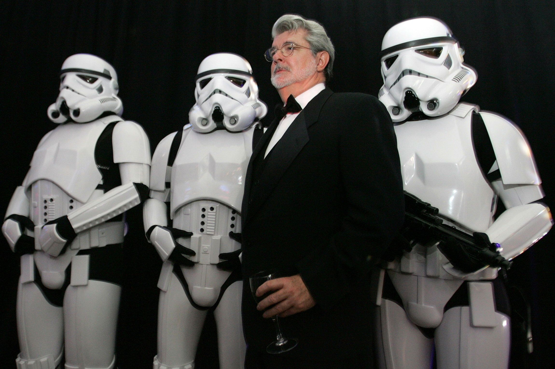 "Star Wars creator George Lucas (2nd-R) poses with Storm Troopers, characters in the Star Wars movies, during a gala held to celebrate the ""Star Wars: Where Science Meets the Imagination"" exhibition at the Museum of Science in Boston, Massachusetts October 22, 2005."