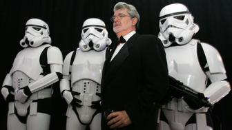 """Star Wars creator George Lucas (2nd-R) poses with Storm Troopers, characters in the Star Wars movies, during a gala held to celebrate the """"Star Wars: Where Science Meets the Imagination"""" exhibition at the Museum of Science in Boston, Massachusetts October 22, 2005."""
