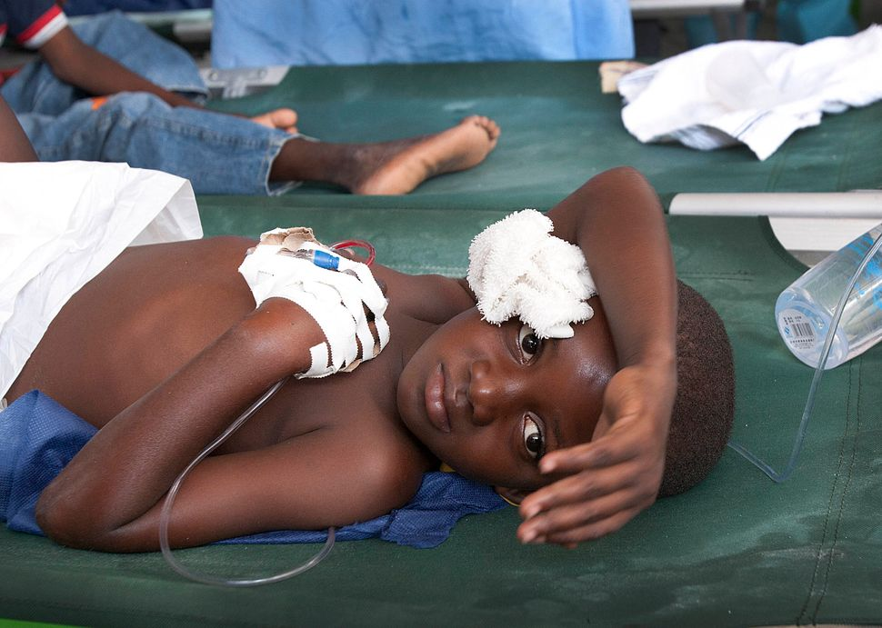Mackenzy Regis, 7, holds his head while suffering from a case of cholera at the International Red Cross station near Port-au-