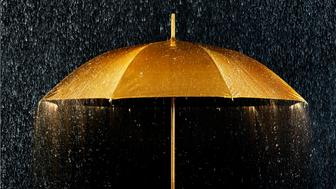 Conceptual photograph of a golden umbrella with rain.