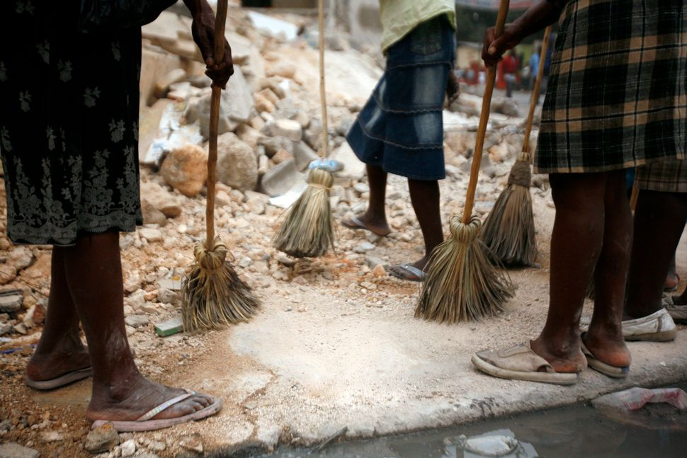 Women clean the rubble and streets of the Carrefour Feuille area of Port-au-Prince on Jan. 26, 2010, as part of a United