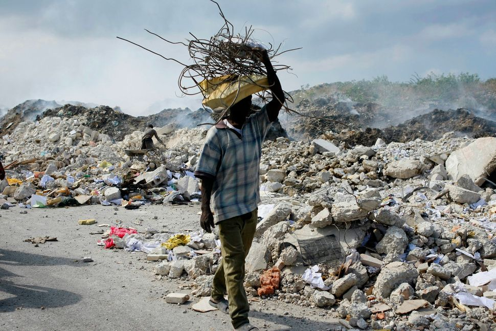 A man carries a bundle of metal bars salvaged from the rubble of collapsed buildings in Port-au-Prince, Haiti, on Jan. 17, 20