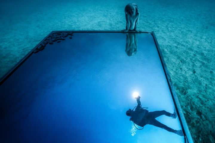 """Portal"" is a half-human, half-animal creature looking into a mirror that reflects the ocean's surface. The mirror is elevated on a platform with small compartments designed to attract octopuses, sea urchins and fish."