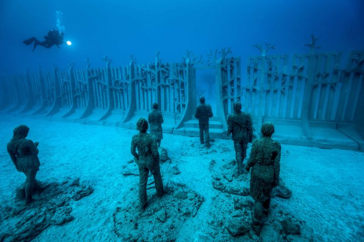 "A diver studies ""Crossing the Rubicon,"" a giant underwater wall installation."