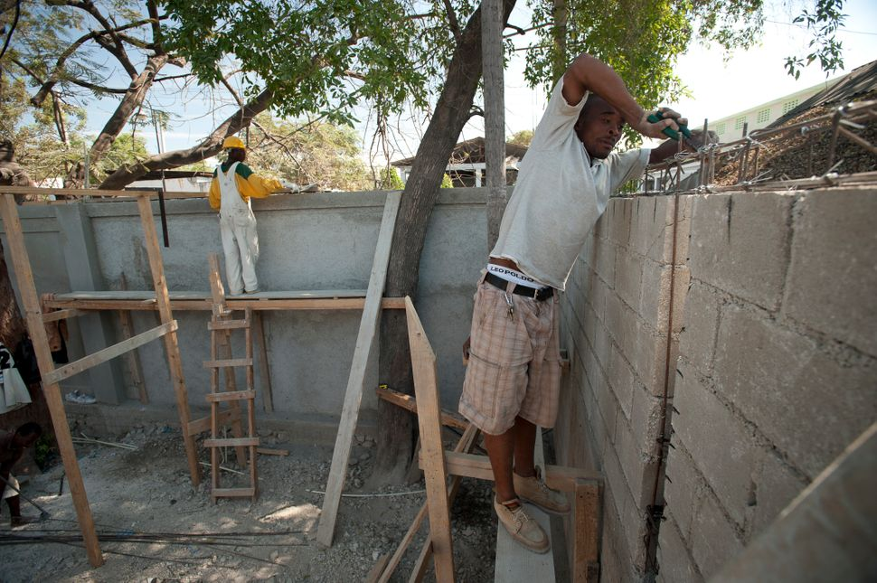 A man ties steel rods together on a walls at Normally High School in Port-Au-Prince on Jan. 11, 2012 as the city co