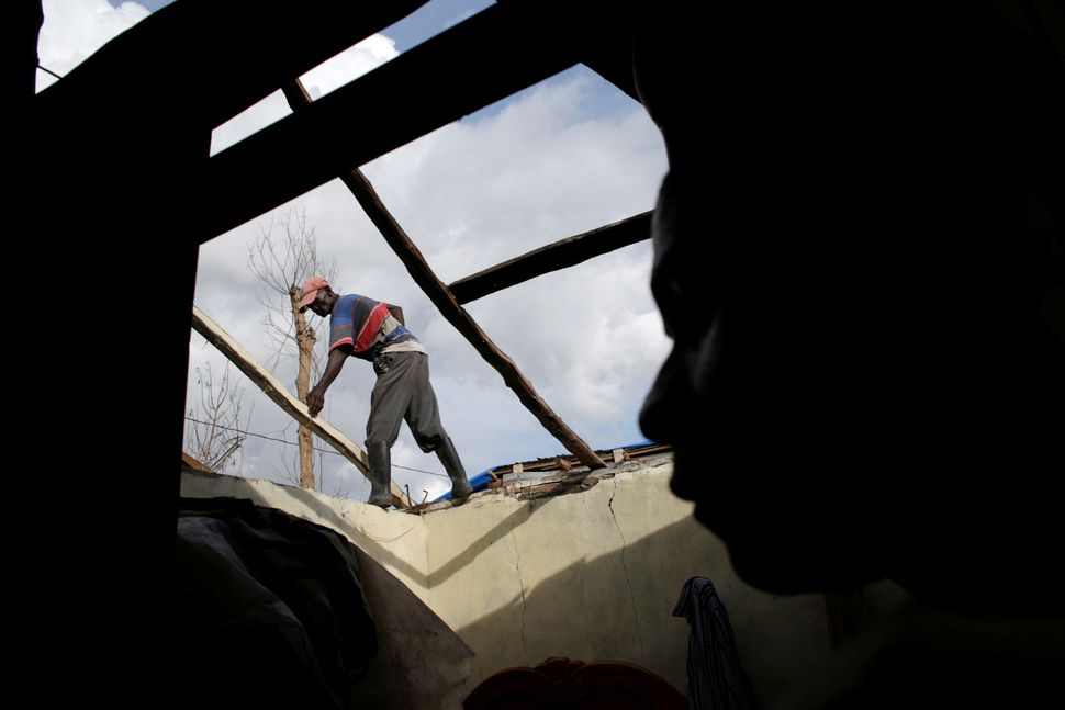 A boy looks at a man as he rebuilds the roof of a house affected by Hurricane Matthew in Damassins on Oct. 22,
